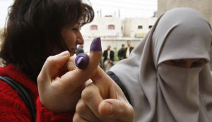Iraqis living in Jordan hold up their ink-stained index fingers after casting their ballot in Amman