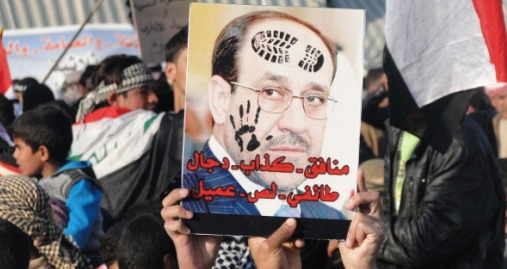 """Iraqi Sunni protestors hold up a portrait of Prime Minister Nuri al-Maliki with slogans reading in Arabic, """"liar...sectarian, thief, collaborator"""" during a protest against him on the main highway to Syria and Jordan near Ramadi, Anbar's provincial capital west of Baghdad, on January 4, 2012. Thousands of Sunnis demonstrated across Iraq on Friday, in the latest of nearly two weeks of rallies criticising the country's premier and demanding the release of prisoners they say are wrongfully held. AFP PHOTO / AZHER SHALLAL (Photo credit should read AZHER SHALLAL/AFP/Getty Images)"""