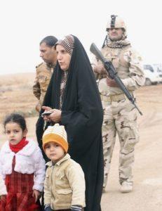 الأهالي الهاربون من العنف بمدينتي الفالوجة والرمادي بالعراق إلى كربلاء، ينتظرون عند نقطة أمنية. 5 يناير/كانون الثاني 2014. © 2014 رويترز