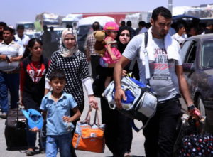 Iraqi families fleeing violence in the northern Nineveh province gather at a Kurdish checkpoint in Aski kalak, 40 kms West of Arbil, in the autonomous Kurdistan region, on June 10, 2014. Suspected jihadists seized Iraq's entire northern province of Nineveh and its capital Mosul, the country's second-largest city, in a major blow to authorities, who appear incapable of stopping militant advances.  AFP PHOTO/SAFIN HAMED