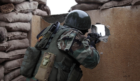Kurdish Peshmerga fighter aims his weapon through a hole in a wall on the front line of fighting against Islamic State militants in the outskirts of Mosul