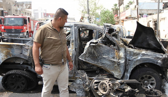 A member of the Iraq security forces looks at the site of a car bomb attack in Baghdad