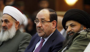 Iraqi Vice President Nuri al-Maliki (C) speaks with Hamid al-Jazaeiri (R), Deputy Commander General of Saraya al-Khorasani, at a ceremony honouring fighters of the group who died during their fight against the Islamic State, in Baghdad February 21, 2015. Families, military personnel and delegates attended the event in Baghdad to honour fighters of the Iraqi Shi'ite militia group formed in 2013 in response to Iran's Supreme Leader, Ayatollah Ali Khamenei's call to fight Sunni jihadists in Syria and later in Iraq. Picture taken February 21, 2015. REUTERS/Ahmed Saad (IRAQ - Tags: CIVIL UNREST POLITICS CONFLICT) - RTR4QM2C